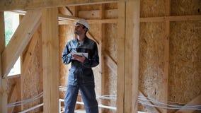 建筑师或建造者检查在一个半建造的木构架房子里计划 木的框架的建筑的工程师 股票录像