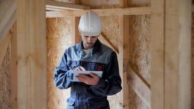 建筑师或建造者检查在一个半建造的木构架房子里计划 木的框架的建筑的工程师 股票视频