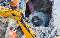 建筑或活跃修理供水照片,下水道或者管子排水系统在具体坑由工作者橙色背心的与 免版税库存照片