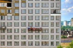 建筑摇篮的工作者在一个大厦的墙壁上建设中与在大厦后的一种都市风景 库存照片