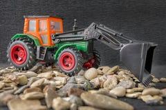 建筑机器车,拖拉机在石渣的玩具模型向背景扔石头 库存照片
