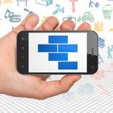 建筑概念:拿着有砖的手智能手机在显示 库存图片