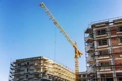 建筑用起重机和未完成的房子 免版税图库摄影