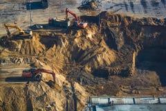 建筑的片刻,开掘与挖掘机的一个垄沟,基础放置 库存图片