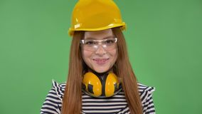 建筑盔甲的年轻人微笑的红发女孩,耳机,风镜,摇她的手,你好标志 股票录像