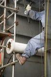 建筑管道安排在上刻锯齿的工作者 免版税库存图片