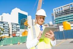 建筑经理控制建筑工地和片剂设备在他的手上 免版税库存照片