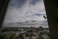 建筑绳索戴一顶安全帽,充分的身体安全带的通入工作者的剪影图片运转在高度,abseiling 免版税库存照片