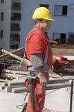 建筑设备垂直的佩带的工作者 免版税库存图片