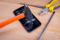 建筑锤子打破智能手机,在它旁边有扁鼻子钳子和螺丝刀 库存图片