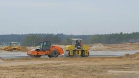 建筑, concreting机场跑道路,高速公路 人,工作者与沥青摊铺机一起使用 Roadroller 影视素材