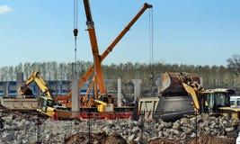建设活动在有推土机、望远镜起重机、樱桃捡取器和挖掘机的城市再开发站点 免版税库存照片