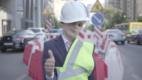 建设者盔甲的疲倦的小男孩在他的看在照相机陈列赞许的头和制服 建筑师概念 股票视频