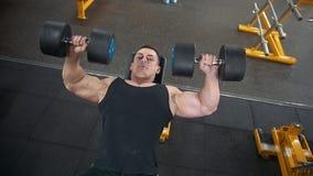 建身在健身房-年轻肌肉人执行二头肌的训练与哑铃-滑子 影视素材