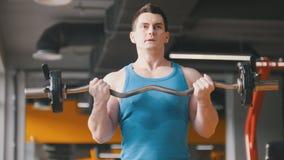 建身在健身房-年轻运动的人执行胳膊的训练与杠铃 免版税库存图片