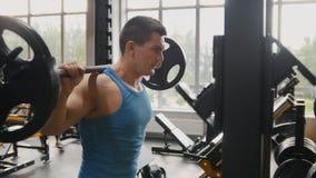 建身在健身房-训练他的二头肌的肌肉人临近镜子 免版税图库摄影