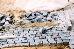 建造场所、工具和细节,路面安装和岩石 放置在沙子的花岗岩石头 免版税库存照片