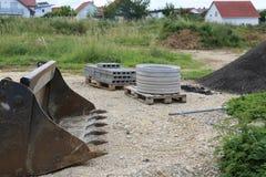 建造场所、挖掘机的瓢和建筑材料 免版税库存图片