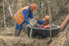 建造场所瓢的工作者浇灌在井外面 免版税库存照片