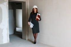 建造场所的女性建筑师有图画和笔记的 免版税库存照片
