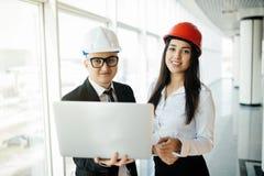 建造场所的小组工程师人和妇女为检查新的项目与膝上型计算机 在旅行之外的新的项目工程师 库存图片