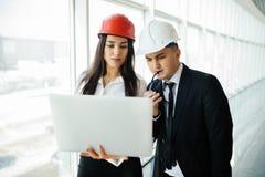 建造场所的小组工程师人和妇女为检查新的项目与膝上型计算机 在旅行之外的新的项目工程师 图库摄影