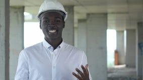 建造场所的非洲工作者谈和看照相机的 库存图片
