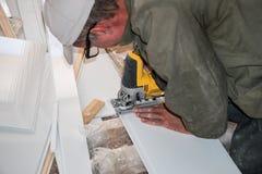 建造者与白色塑料零件一起使用 库存图片