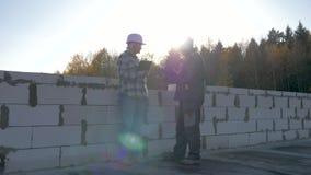 建造者和客户盔甲的和风镜在工地工作站立反对太阳 股票录像