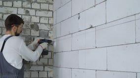 建造者在块墙壁和插入定缝销钉的钻孔 影视素材
