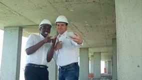 建造者愉快的微笑的作为selfie照片队在关于建造场所的会议期间 股票录像