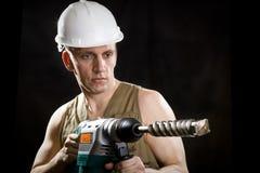 建造者拿着专业穿孔机 免版税库存图片