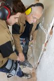 建造者拿着在地板上的电钻 图库摄影
