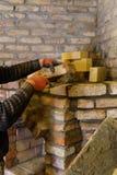 建造者放下壁炉的砖并且紧固他们与水泥灰浆 库存照片