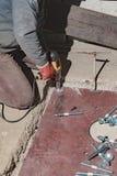 建造者转动有一把电板钳的坚果 库存照片
