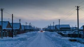离开一个积雪的村庄的汽车 免版税库存照片