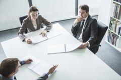开三个的商人坐在桌附近和业务会议,大角度看法 免版税图库摄影