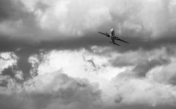 离开与多云天空的飞机 免版税图库摄影