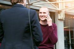 开业务会议谈话在街道上和打电话的年轻成人企业家人民 库存图片