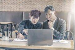 开两个可爱的商人与膝上型计算机的一次会议,当食用咖啡时 免版税库存图片