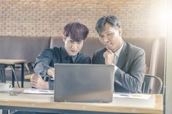 开两个可爱的商人与膝上型计算机的一次会议,当食用咖啡时 库存图片