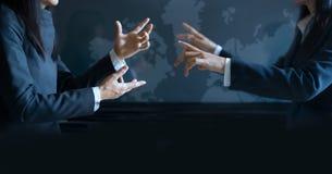开两名的女实业家关于虚屏背景的谈的非正式会议 免版税库存图片