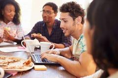 开会议和吃薄饼的商人 免版税库存图片