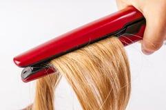 开创性 与电头发铁直挺器的特写镜头白肤金发的妇女长发制造的发型发型 免版税库存照片