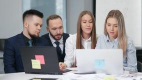 开办公室工作者的同事谈论队的会议看膝上型计算机个人计算机的屏幕新的项目 股票录像