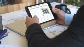 开发企业项目和分析关于平板电脑的年轻商人的男性手统计数字信息 股票视频