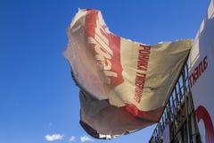 开发在天空中的被撕毁的广告牌反对天空蔚蓝 免版税库存图片