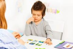 开发比赛的被集中的男孩戏剧在桌上 免版税库存照片