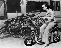 离开在尘土,一个少妇花梢骑自行车缩样摩托车(所有人被描述不是更长生存和没有esta 库存图片