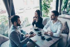开大角度观点的三个年轻的商务伙伴会议 免版税库存照片